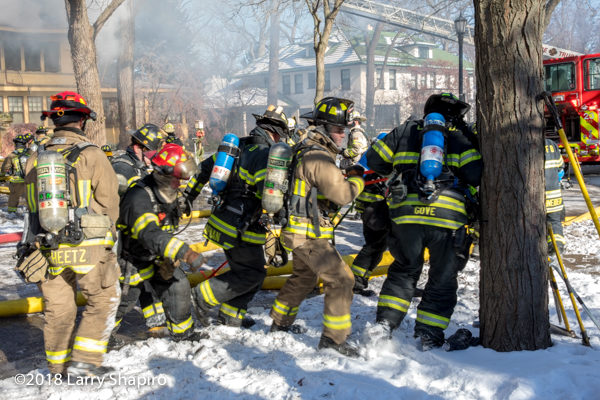 firefighters work together moving LDH