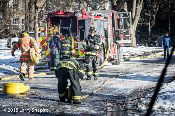 firefighters roll hose after winter fire