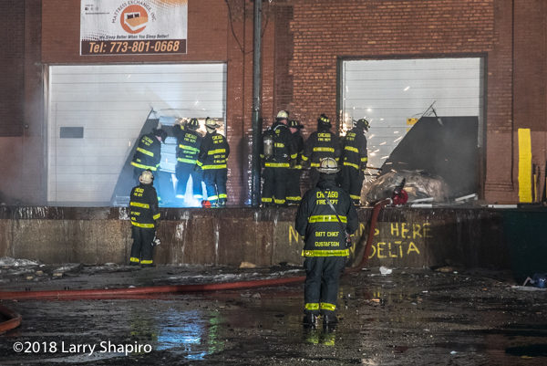 Chicago firefighters cut overhead doors with saws