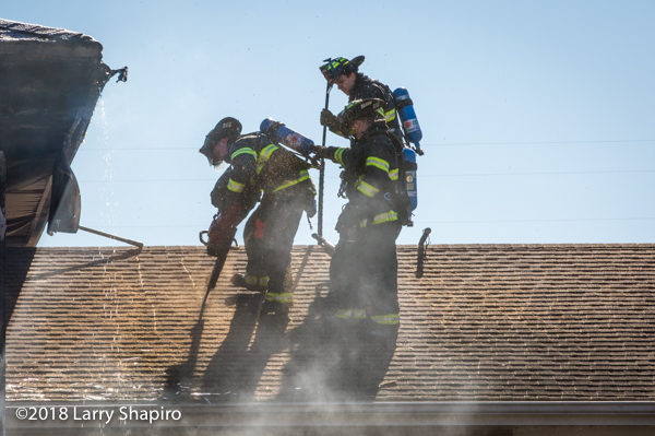 firefighters ventilate roof with a saw