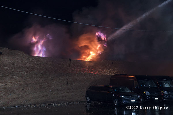 flames through the roof of commercial building