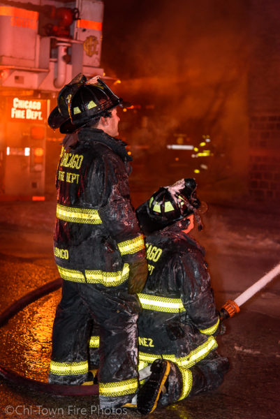 firefighters battle a fire at night