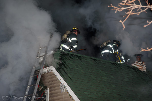 Firefighters on roof of house on fire
