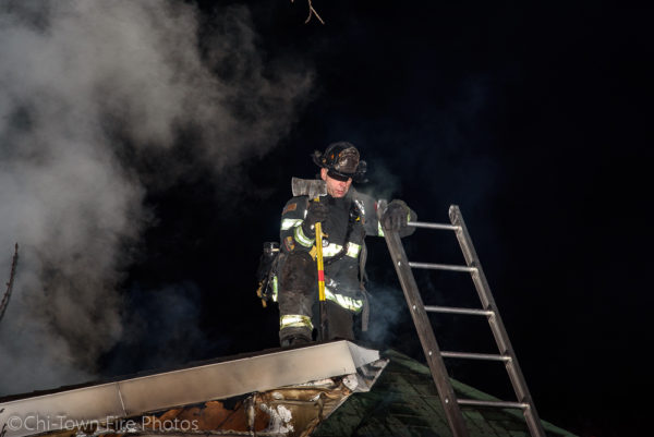 Firefighter on roof during house fire