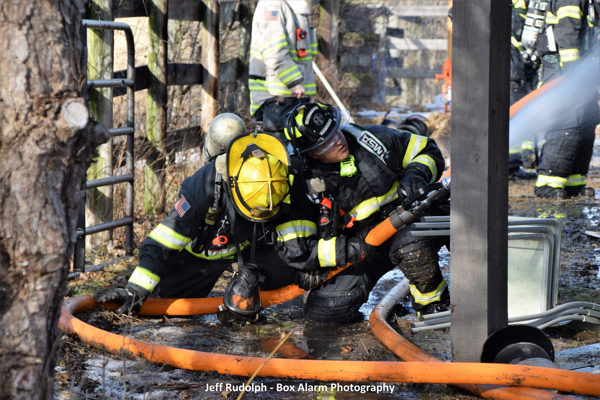 firefighters man a hose line