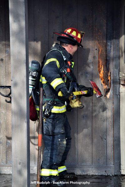 firefighter uses an axe to break a door