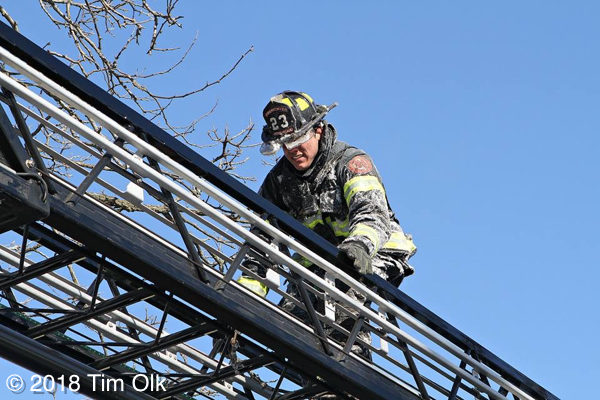 firefighter climbs aerial ladder with ice