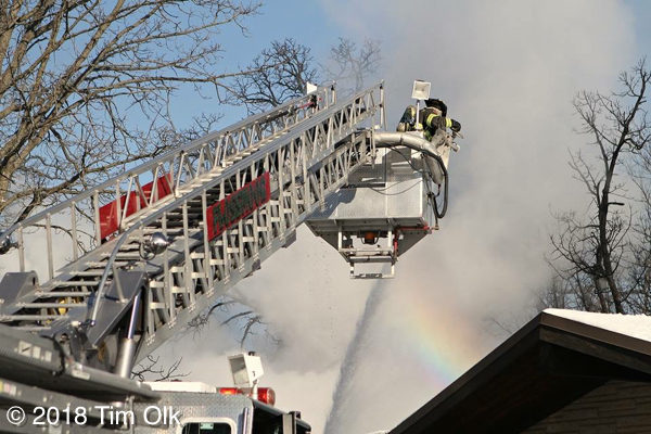 firefighters in Sutphen tower ladder at fire