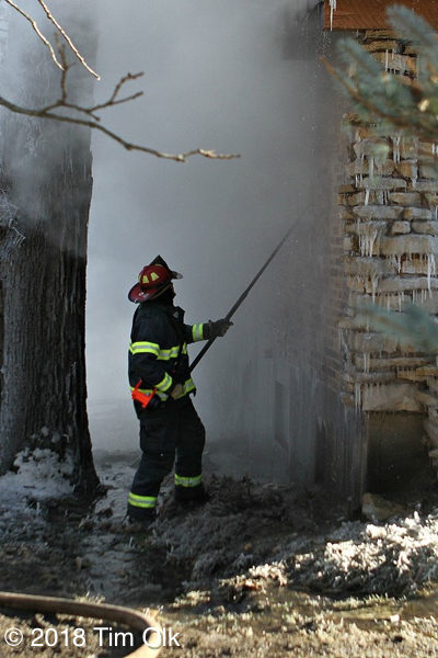 firefighter overhauls after winter house fire