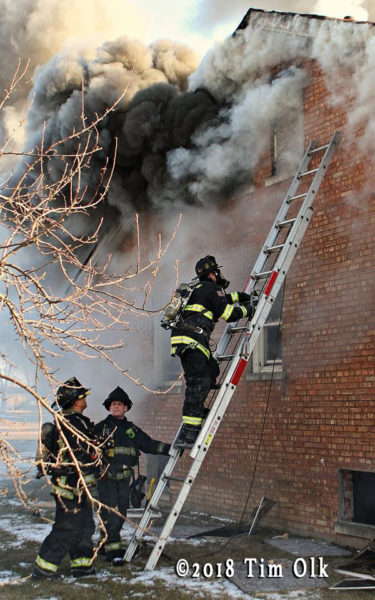 firefighter on ladder with heavy smoke