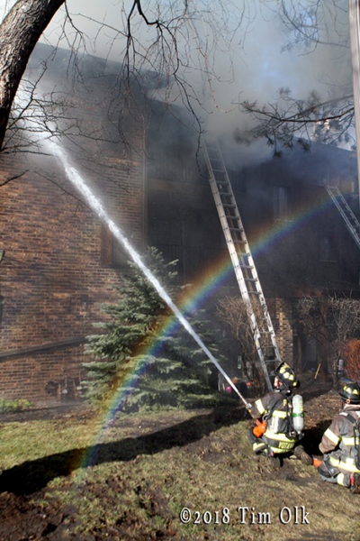 firefighters with hand line and rainbow at fire scene