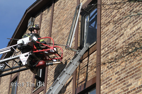 firefighter on aerial ladder overhauls after fire