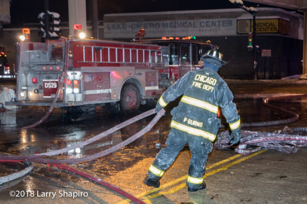 Chicago Firefighter pulls hose in the cold