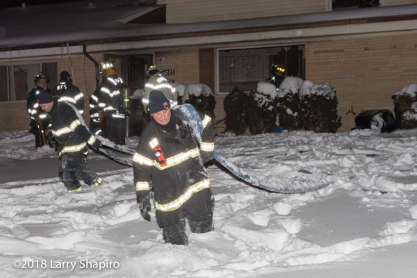 Firefighter pulls hose through a foot of snow