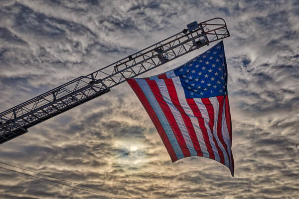 American flag suspended from a fire truck ladder