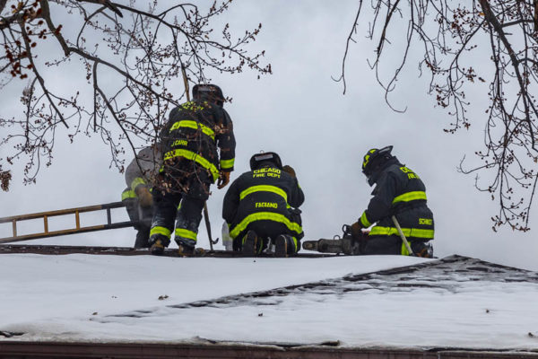 Firefighters on roof with stripping ladder