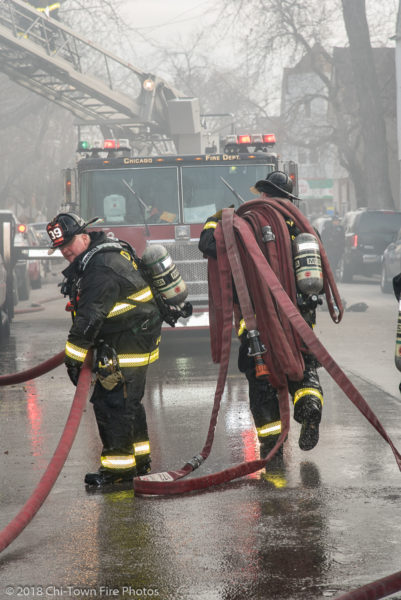 Firefighters carry hose in the street
