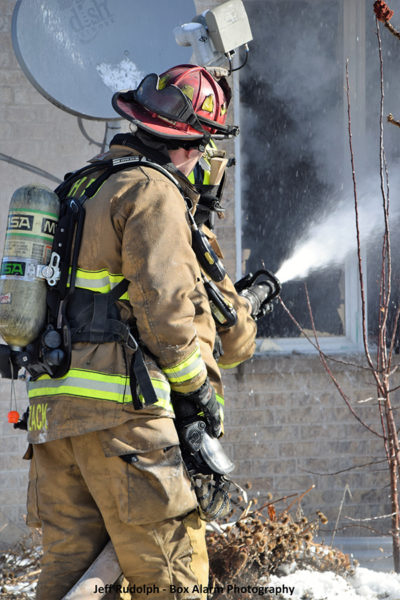 Firefighters with hose line battle a fire