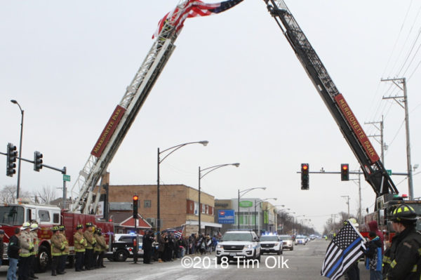 funeral procession passes under aerials with flag