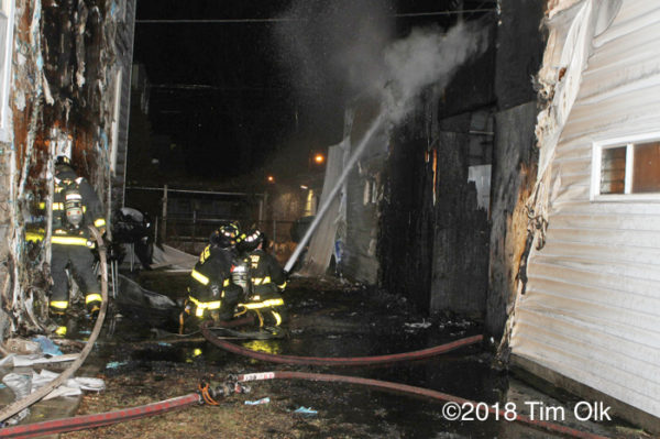Firefighters after alley garage fire