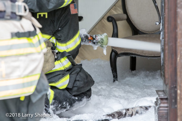 Firefighters with hose line immersed in foam