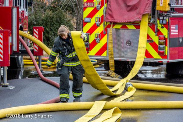 Female Firefighter pulls hose