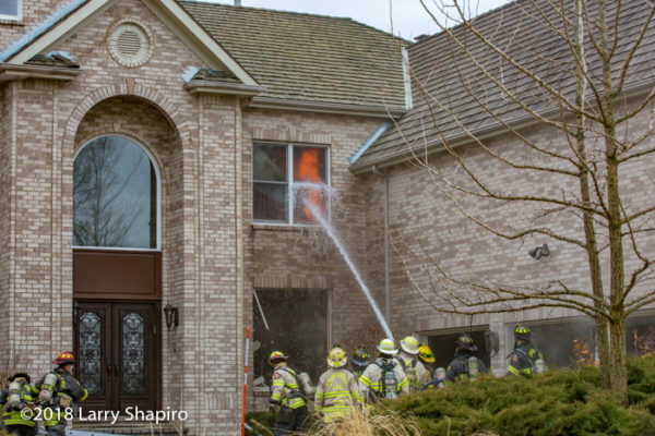Firefighters with hose apply water to fire
