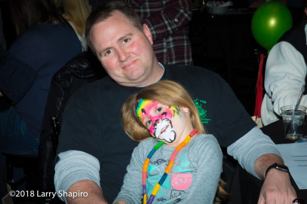 girl with great cat face painting in father's lap