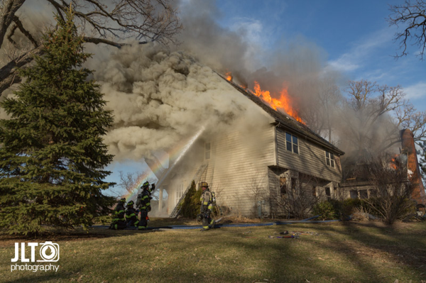 Firefighters battle house fire with flames