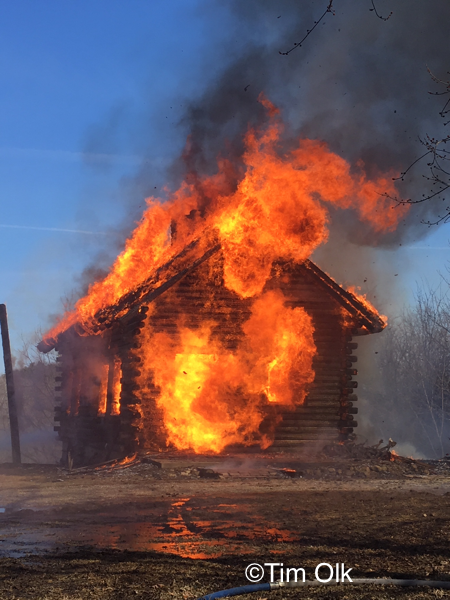 log cabin house engulfed by fire