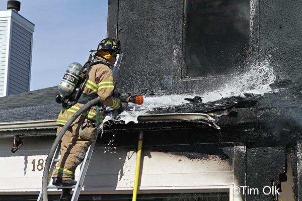 Firefighter washes down a roof after a house fire