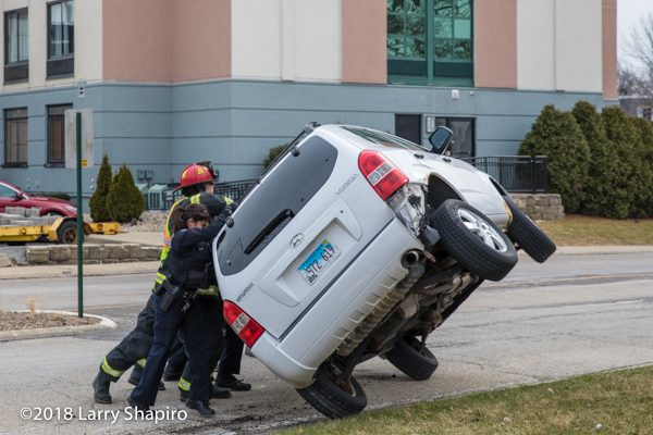 police officers and Firefighters roll car onto the wheels