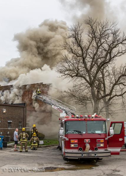 Firefighters battle building fire with heavy smoke