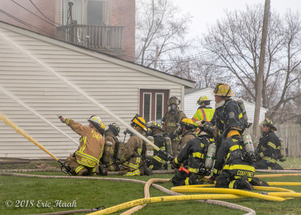 Firefighters operate multiple hose lines at fire scene