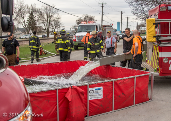 fire department water tender dumps into a portable tank