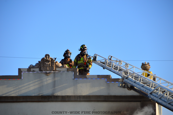Firefighters on building roof with aerial ladder