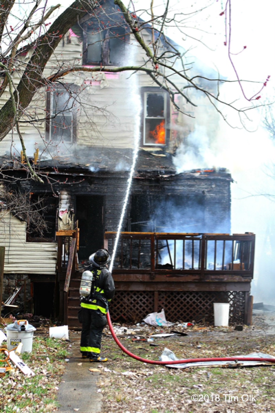 Firefighter with hose at house fire