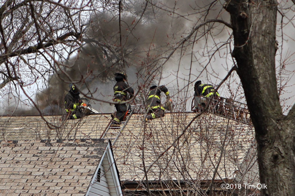 Firefighters venting house roof