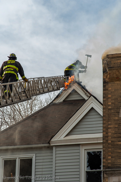 Firefighters vent roof with an axe