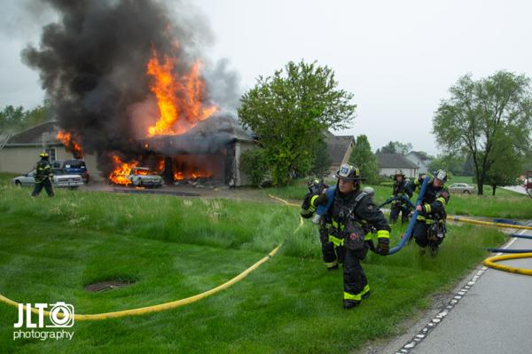 Firefighters drag hose line at fire scene