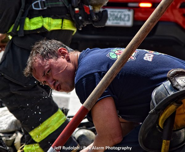 Firefighter sweating after battling fire in hot weather