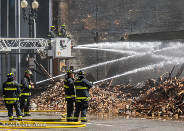 Firefighters pour water on building ruins