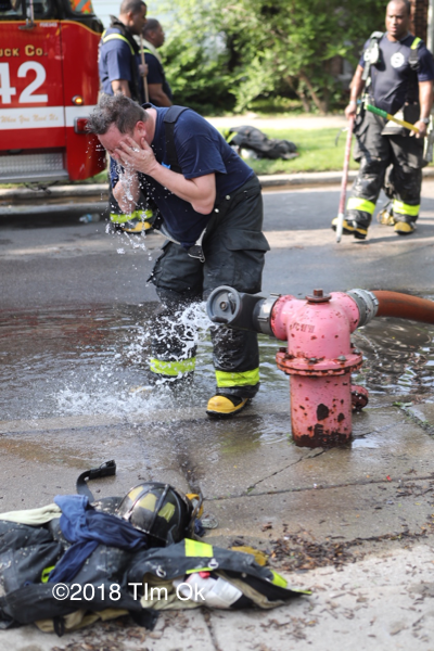 Firefighter cooling off by a hydrant