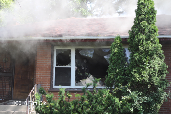 Firefighter vents window of house fire