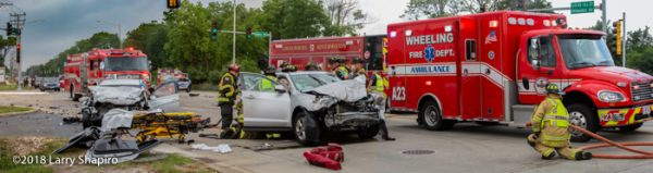 Firefighters work to extricate victims after a crash