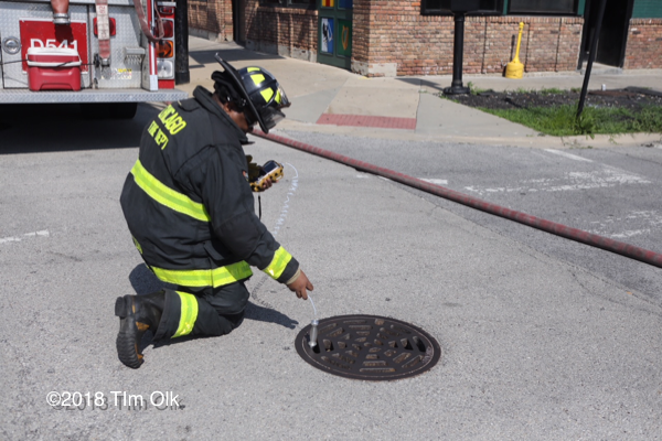 Firefighter takes gas reading in sewer