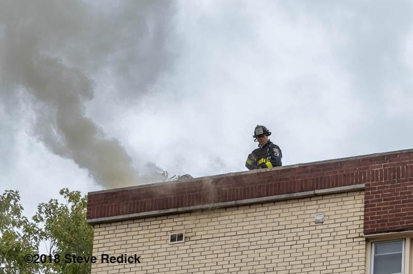 Firefighter and smoke from roof of apartment building