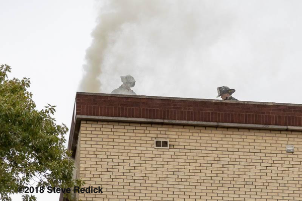 smoke from roof of apartment building