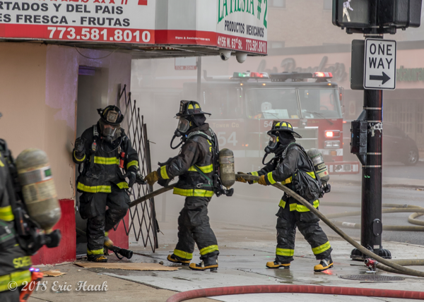Chicago Firefighters take a line into a burning building