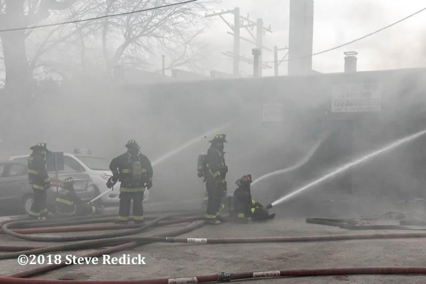 Firefighters battling a smokey fire without SCBA